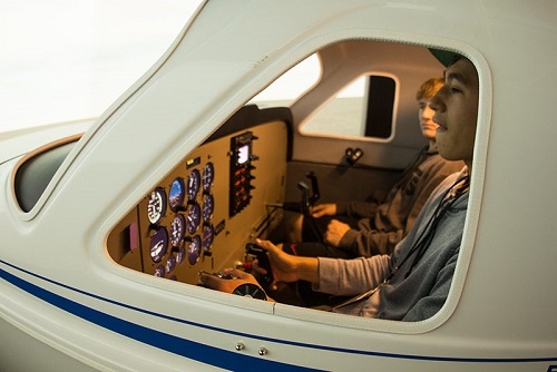 "PUC students ""fly"" the Frasca 180 flight simulator."